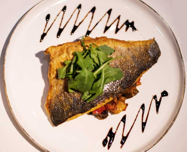 Branzino, a Mediterranean sea bass on fall ratatouille
